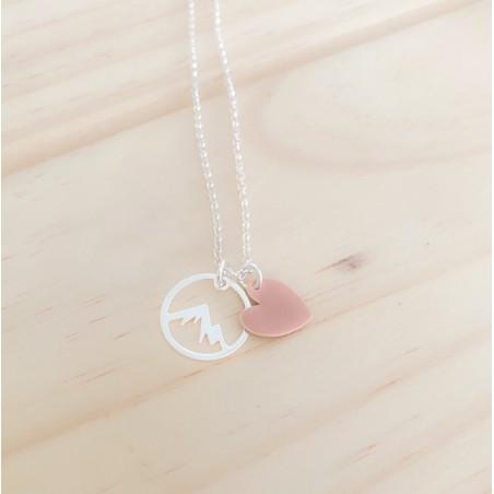 cadena de plata de ley con dos colgantes, uno redondo con forma de montaña y el otro es un corazón esmaltado en rosa